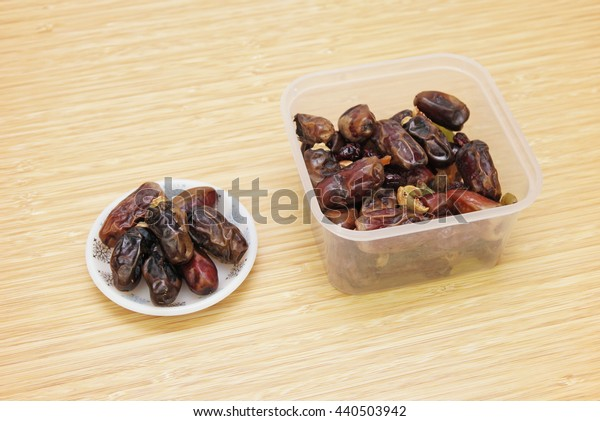 dates in a small plate and a rectangular plastic container.
