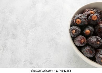 dates in a white bowl closeup, copy space