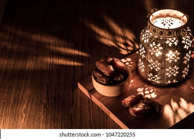Dates in wooden bowl and Arabian lantern on wooden floor. Eid lamp or lantern for Ramadan and other Islamic Muslim holidays, with copy space for text