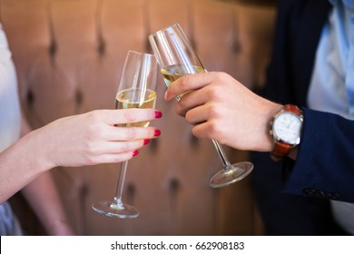 dating concept - close up of champagne glasses in male and female hands