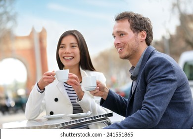 Dating couple drinking coffee at sidewalk cafe outdoors on date. Young beautiful professionals talking enjoying espresso laughing having in Barcelona, Spain near Arc de Triomf on Passeig de Sant Joan.