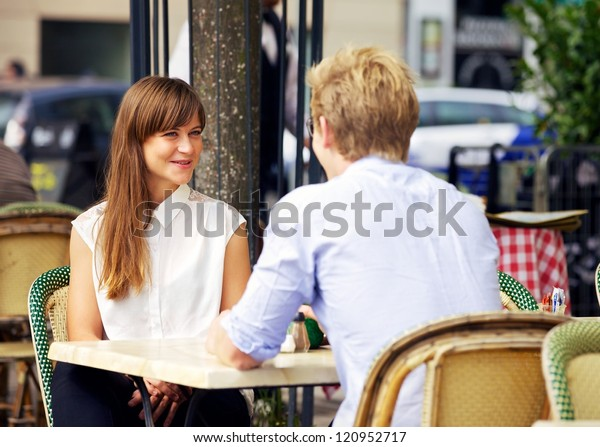 Dating couple enjoying the outdoors in a Parisian cafe