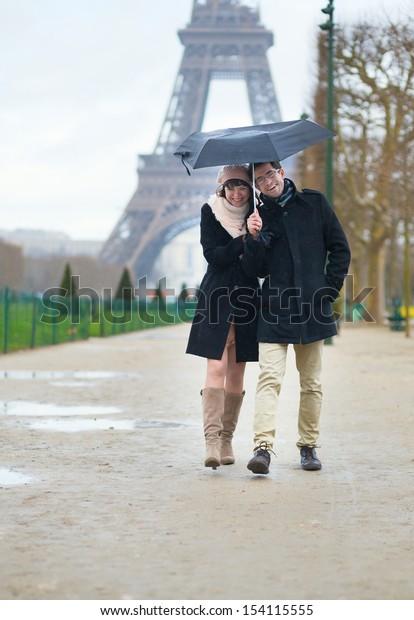 Dating couple under the rain in Paris