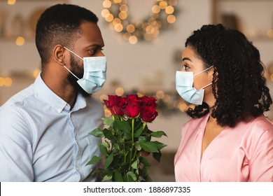 Dating During Pandemic. African american couple wearing medical face masks, spending time together at home or cafe, holding bouquet of red roses flowers. New normal, coronavirus, covid