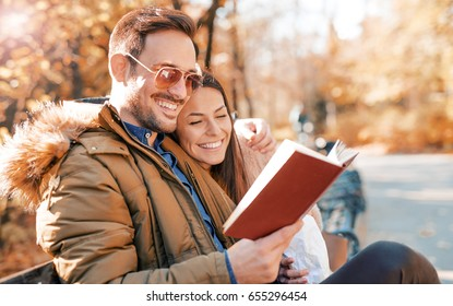 Dating in the park. Handsome loving couple sitting on the park bench and reading a book, having fun together. Love and tenderness. Dating, relationships, friendships, education, lifestyle concept