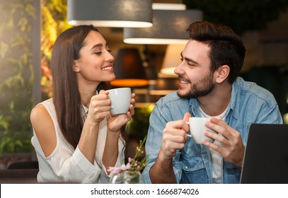 Dating. Young couple tasting coffee drinks enjoying flirt and conversation during weekend date sitting in cozy cafe