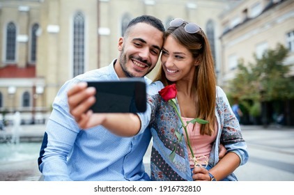 Dating. Young loving couple sitting in the city park and taking a selfie with smartphone. Dating, love, relationships, lifestyle concept