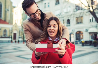 Dating. Young man surprised his girlfriend with a present. Love and relationships concept