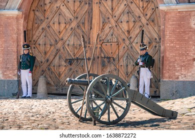 Daugavpils, Latvia - July 20, 2019 : Re-enactment festival Dinaburg 1812 in Dinaburg Fortress. Re-enactors of Russian Imperial army are guarding closed gates with cannon replica in the foreground.