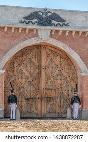 Daugavpils, Latvia - July 20, 2019 : Re-enactment festival Dinaburg 1812 in Dinaburg Fortress. Re-enactors of Russian Imperial army of Napoleonic era are guarding closed wooden Nicholas gates.