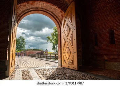 Daugavpils/Latvia-07.22.2020: Wooden bridge through the arch of the main gate of Daugavpils Fortress. Nicholas Gate was built in 1827 in Neo-Gothic style – best restoration project in 2013 in Latvia.