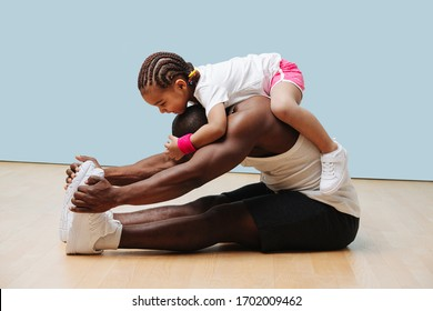 Daughter climbes on her father's neck as he stretches his back and knees on the floor. They having fun, entertaining themselves in isolation.
