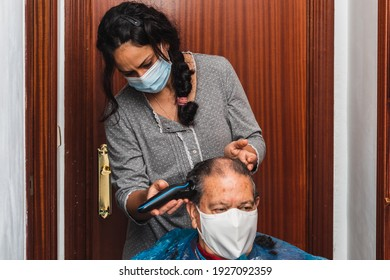 Daughter cutting her father's hair at home