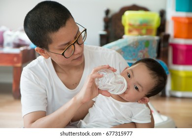 The daughter is drinking water from a nursing bottle with a mother carrying her.