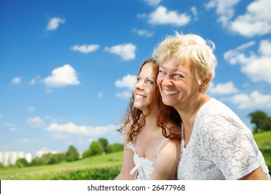 The daughter and elderly mother against the sky and park