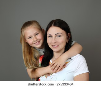 Daughter embraces her mother on gray background - motherhood, family relationships,happiness and love concept