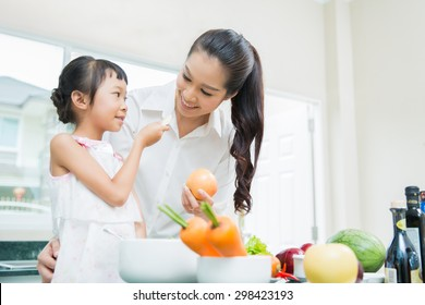 The daughter is entering her mother eating fruit. While cooking in the kitchen