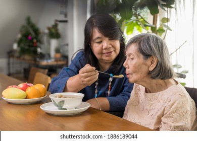 Daughter feeding elderly mother with soup.