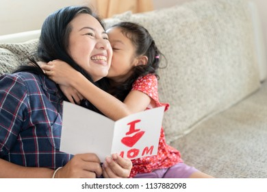 Daughter give mother day greeting card to mom