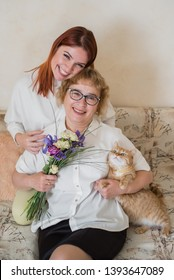 Daughter gives a bouquet to an adult mother sitting on a sofa in the living room. Spending time together, celebrating at home on weekends. Mothers Day. Cat eats flowers