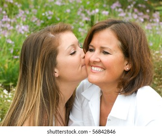 Daughter gives her mom a kiss on the cheek