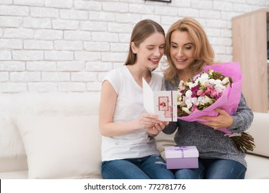 The daughter gives her mother flowers and gifts. She makes her a surprise. Mom is very surprised. They are together at home.