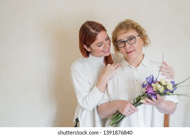 Daughter giving flowers to adult mother. Daughter gives flowers to her mother and hugs her. Spending time together, celebrating at home on weekends. Mothers Day