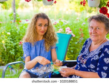 Daughter giving money as birthay present for retired mother in rehabilitation.