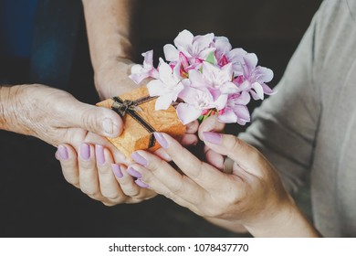Daughter hand giving present box for the mother on Mother's day