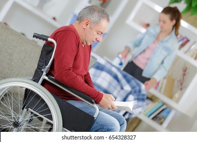 daughter helping father in wheelchair at home