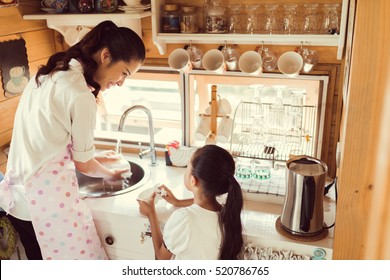 Daughter helping her mother in the kitchen washing dishes, washing the glass.