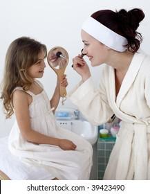 Daughter helping her mother in makeup in bathroom
