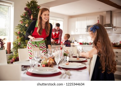 Daughter Helping Mother To Lay Table As They Prepare For Christmas Meal At Home