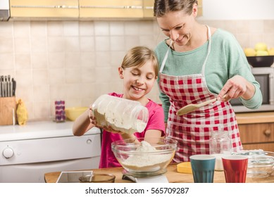 Daughter helping mother to making  pizza dough in the kitchen