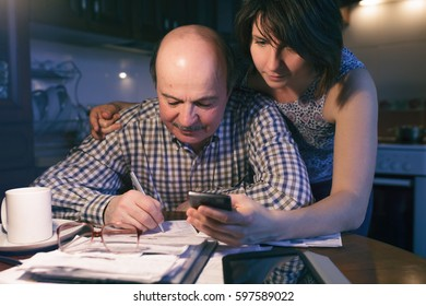 daughter helps her father count money and manage the family budget