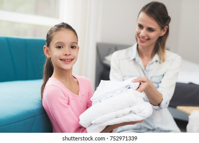 The daughter helps the mother with household chores. They are sitting on the floor in a bright room. My daughter is happy to help her mother.