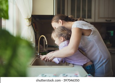 Daughter with her mother to wash their hands in the kitchen sink,. casual lifestyle photo series in real life interior,toning