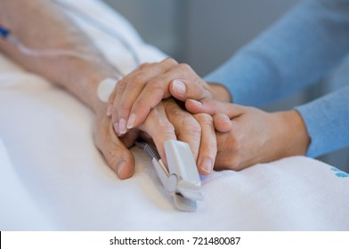 Daughter holding the hand of an elderly father. Closeup of woman holding senior man hand in hospital. Close up of nurse holding old man hand with oxygen saturated probe on finger.
