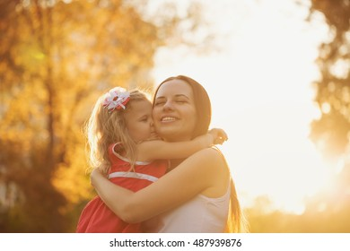 Daughter hugging her mother. Mother and baby girl together. Family time. The joy of motherhood.