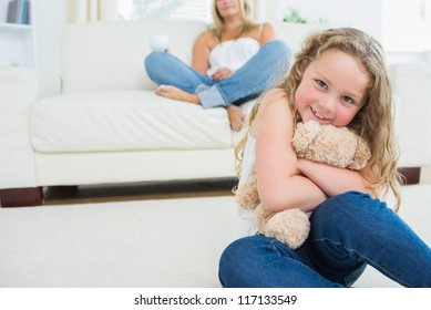 Daughter hugging her teddy bear while her mother is resting on the sofa