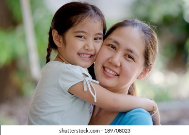 Daughter hugging mother Asian family