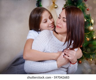 Daughter hugging mother under Christmas tree