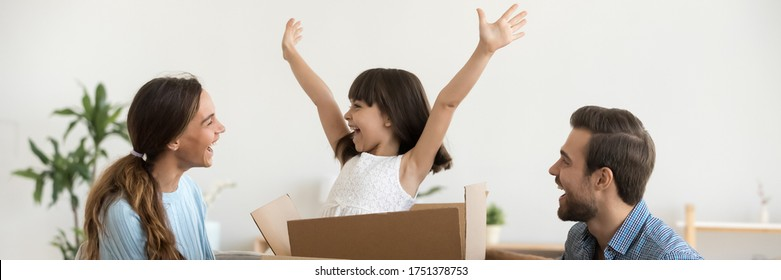 Daughter jumps out of box at moving day at new home with loving parents, family have fun unpack their belongings start new life at first house concept horizontal photo banner for website header design
