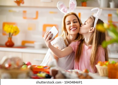 Daughter kiss her mother on selfie in kitchen for Easter
