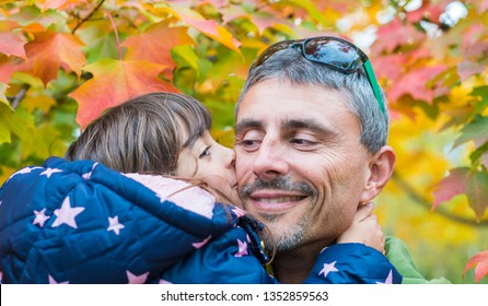 Daughter kissing father with foliage background. Family and love concept.