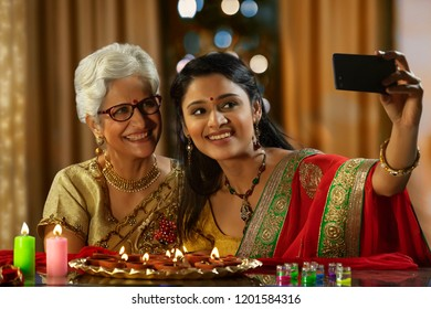 Daughter in law taking a self portrait with mother in law on the occasion of Diwali