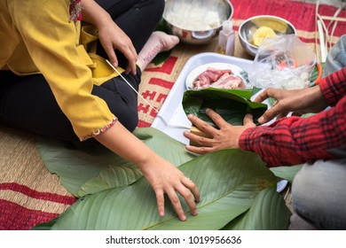 The daughter learning to make Chung cake by hands with his father closeup, Chung cake is the most important traditional Vietnamese lunar New Year (Tet) food.