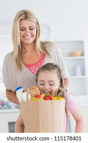Daughter looking into grocery bag with mother watching in the kitchen