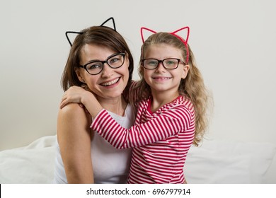 The daughter lovingly embraces her mother. Parent and child in glasses.