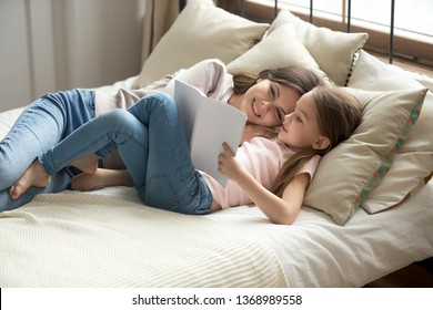 Daughter and mom resting lying on bed resting having lazy weekend at home, little kid girl holding fairy tale book reading interesting story to mum spend time together, good hobby, smart child concept